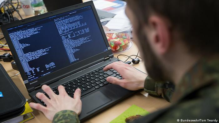 German military man working at computer with code on the screen