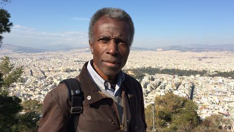 Ο Ακινμπόντε Ακινμπιγί είναι φωτογράφος και εικαστικός καλλιτέχνης με νιγηριανή-βρετανική καταγωγή. Εδώ και χρόνια φωτογραφίζει πόλεις, από το Λάγος ως το Βερολίνο. Στην Αθήνα θέλει να αποτυπώσει μέσα από τον φακό του τα πολλά πρόσωπα της πόλης, αλλά και να δει μέσα από την ελληνική μεγαλούπολη τον δυτικό πολιτισμό.