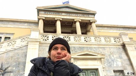 Η εικαστικός Γεωργία Σαγρή φωτογραφίζεται μπροστά από το Πολυτεχνείο, το κατεξοχήν σύμβολο αντίστασης στη σύγχρονη ελληνική ιστορία. Η documenta εστιάζει στο Πολυτεχνείο, με πολλές εκδηλώσεις να περιστρέφονται γύρω από αυτό.