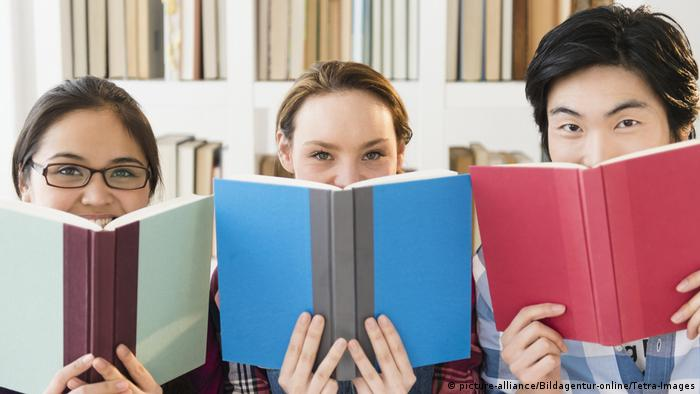 Three young people holding up books (picture-alliance/Bildagentur-online/Tetra-Images)