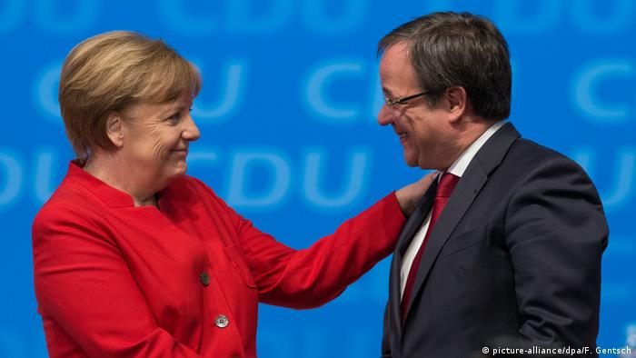 Angela Merkel puts her hand on Armin Laschet's shoulder, they are smiling at each other
