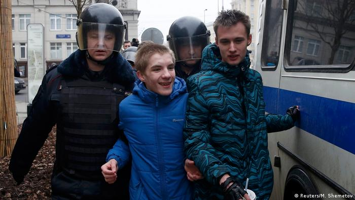 Полицейские ведут задержанных молодых людей во время антиправительственного протеста в Москве в апреле 2017 года