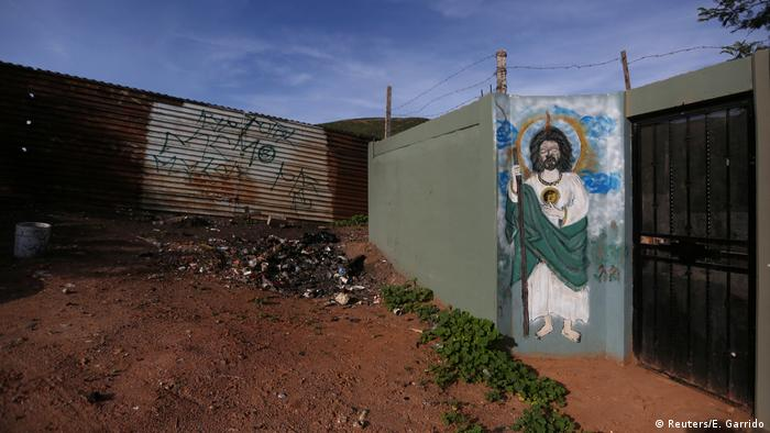 A wall next to a section of border fence on the outskirts of Tijuana, Mexico