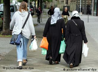 Women wearing head scarves and carrying plastic bags