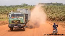 A truck on a dusty road with a palm oil plantation in the background (Bjoern Kietzmann)