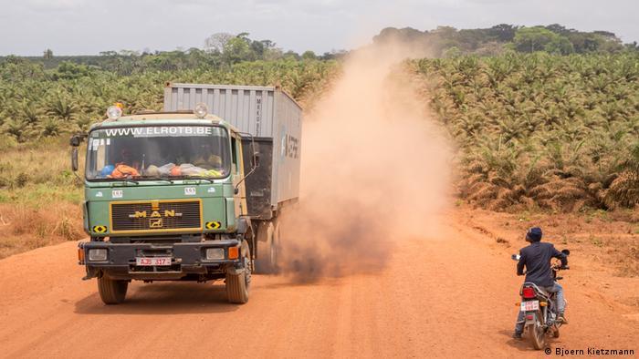 Ein LKW fährt über eine Sandstraße in einer Palmölplantage