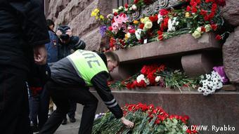 Сотрудник ДПС возлагает цветы к мемориалу