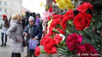 Люди возлагают цветы у станции метро