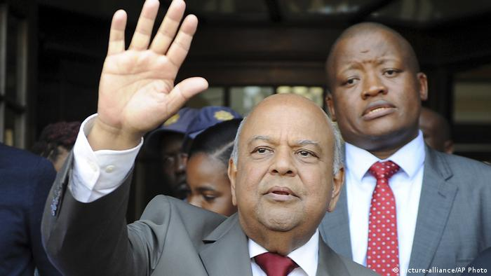 Former Finance Minister Pravin Gordhan gestures with his hand towards a crowd behind the camera