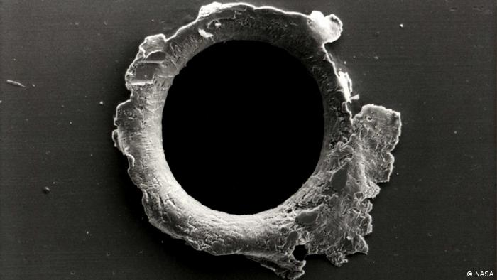 A hole ripped into a spacecraft by space debris