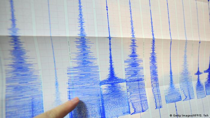A man points at a seismic chart at a weather bureau (Getty Images/AFP/S. Yeh)