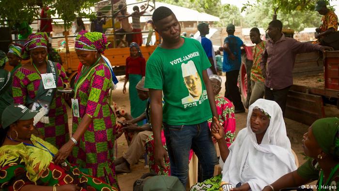 Ein Mann in einem grünen T-Shirt mit dem Portrait Jammehs und der Aufschrift Wählt Jammeh.