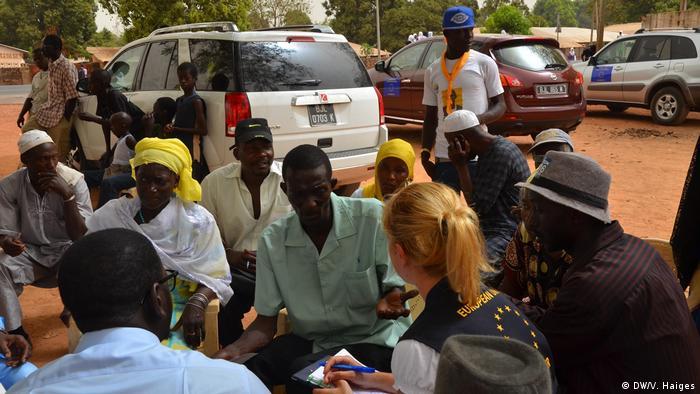 Eine Wahlbeobachterin mit einer blauen Weste mit dem Sternenlogo der EU spricht mit Wählern.