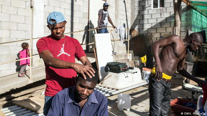 A Haitian man gives another Haitian a haircut at the Canyon of Scorpions, outside Tijuana, Mexico