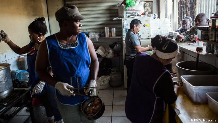 Haitian migrants serve food from the kitchen of a restaurant in Avenida Ocampo in central Tijuana, Mexico