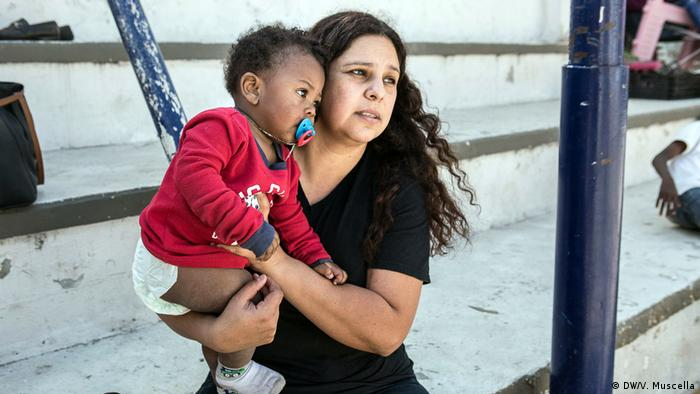Pastor's wife Alvidrez holds a Haitian child in her arms at the Emmanuel Baptist Center in Tijuana