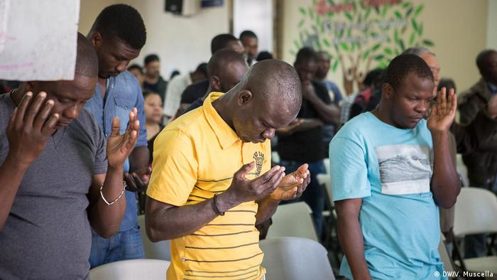 Haitian migrants pray during a mass at a shelter opened by Catholics