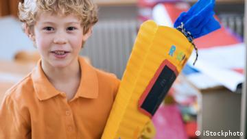 Ein Junge mit einer Schultüte in der Hand.