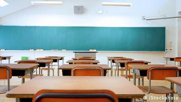 Leeres Klassenzimmer mit Tischen, Stühlen und einer Tafel.