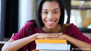 Eine junge Frau hat ihre Hände auf einen Stapel Bücher gelegt und lächelt.
