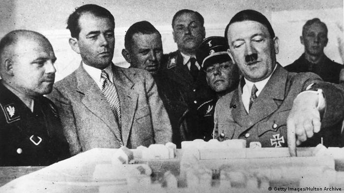 Adolf Hitler (right) discussing plans for a new administration building with Albert Speer (second from left) in 1936 (Getty Images/Hulton Archive)