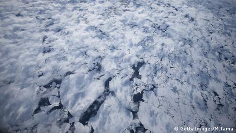Broken sea ice can be seen through light cloud cover mid-flight during last season's Operation IceBridge near the cost of West Antarctica on October 28, 2016.