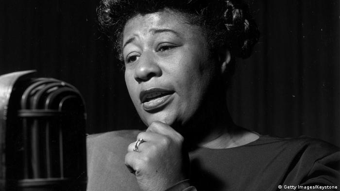 Ella Fitzgerald standing in front of a microphone