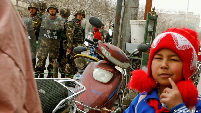 Uighur child next to security forces in Xinjiang, China (Reuters/T. Peter)