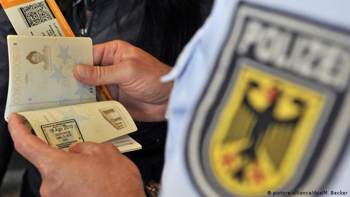 A German police officer looking at a passport (picture alliance/dpa/M. Becker)
