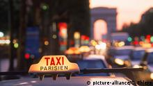 Taxicabs and traffic at dusk on Champs Elysees with Arc de Triomphe in Paris | Verwendung weltweit