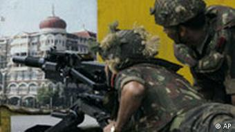 Army personnel lie down and aim a grenade launcher at a part of the facade of the Taj Mahal hotel