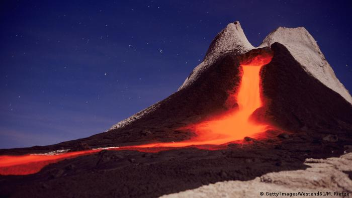 Volcano in front of evening sky: bright red-orange lava flows out