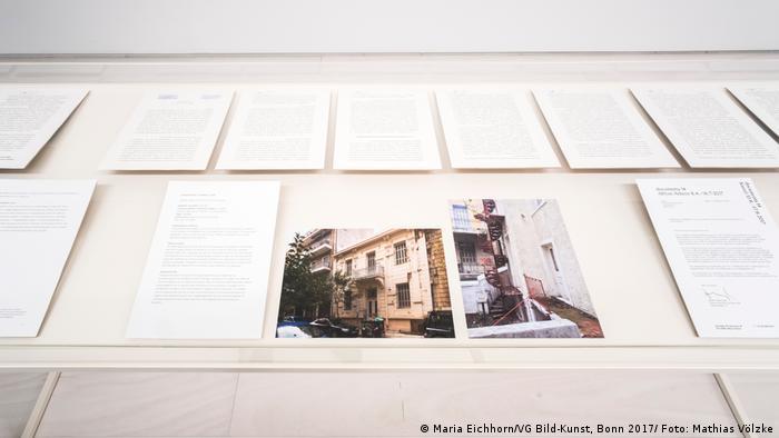 In einer Vitrine liegen Fotos und Schriftstücke zu einem Immobilienkauf in Athen.