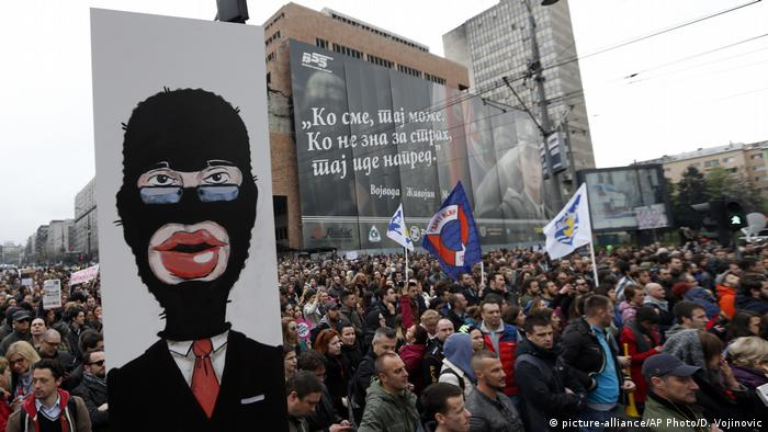 A protester holds a banner depicting PM Aleksandar Vucic, during a protest in Belgrade on April 8.