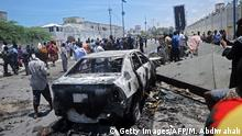 EDITORS NOTE: Graphic content / People stand at the site of a car bomb near a restaurant near the Somali ministry of internal security in Mogadishu on April 5, 2017. At least seven people were killed and 10 wounded on April 5 when a car bomb exploded at a restaurant near the Somali ministry of internal security in Mogadishu, officials said. / AFP PHOTO / Mohamed ABDIWAHAB (Photo credit should read MOHAMED ABDIWAHAB/AFP/Getty Images)
