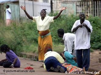 People in the Nigerian city of Jos cry as someone is lying on the ground during clashes in 2001