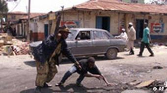 A soldier throws to ground a suspected troublemaker in Jos in September 2001