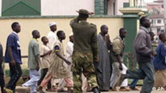 A soldier disperses Muslims gathered at Massalachi Juma mosque in Jos in 2001