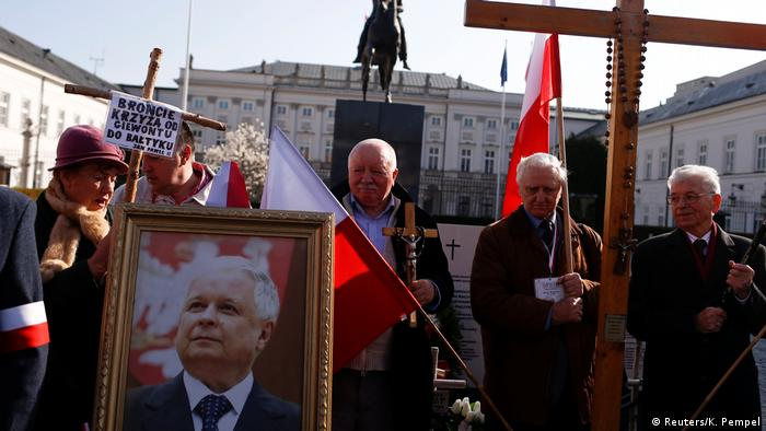 People carrying Polish flags mark the 7th anniversary of the Smolensk plane crash that killed President Lech Kaczynski, whose photo they carry