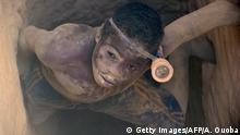TO GO WITH STORY BY JORIS FIORITI A young miner exits the well of a clandestine gold mine on February 20, 2014 in the village of Nobsin, 10km from the city of Mogtedo in the Ganzourgou region, where the gold fever doesnt spare children who risk their lives trying to find a way to survive. AFP PHOTO / AHMED OUOBA (Photo credit should read AHMED OUOBA/AFP/Getty Images)
