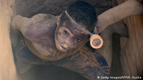 A boy crawls out of a gold mine in Burkina Faso
