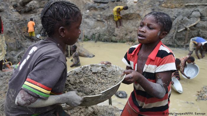 Zwei Kinder halten eine Schüssel mit Erde in einer Goldmine