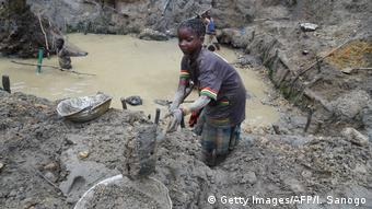 A child miner looks for gold