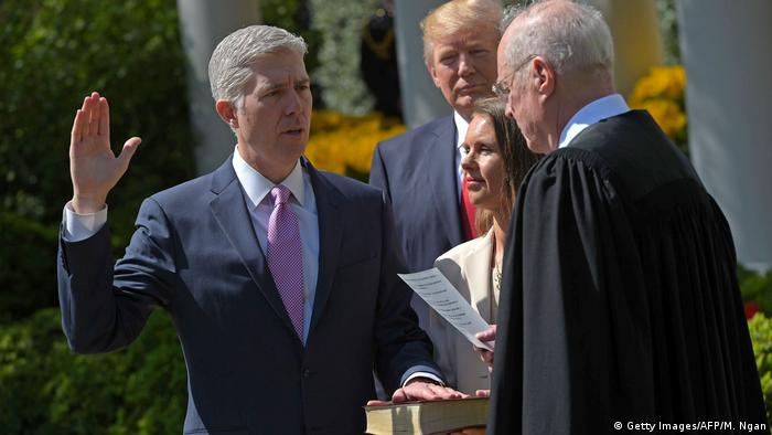 US President Donald Trump (C) watches as Justice Anthony Kennedy (R) administers the oath of office to Neil Gorsuch (L)as an associate justice of the US Supreme Court in the Rose Garden of the White House on April 10, 2017 in Washington, DC.
