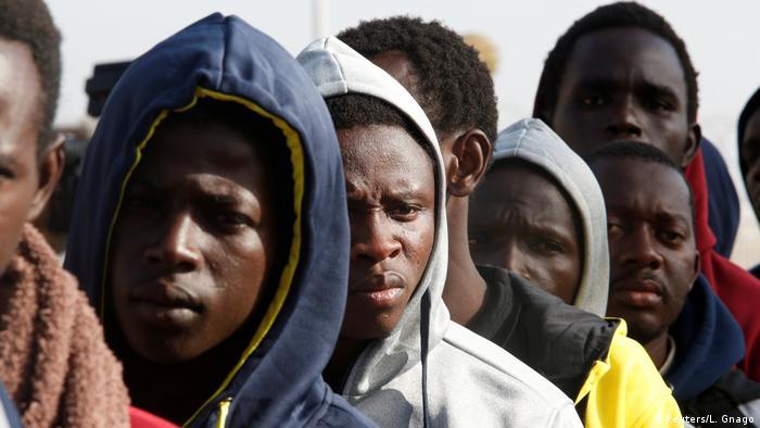 Freiwillige Rückkehrer aus Libyen stehen auf dem Flughafen in Banjul in einer Schlange