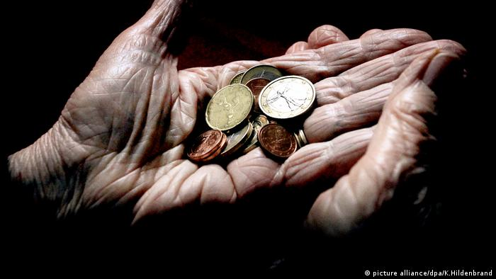 An old woman holds coins in her hands