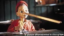 Holzfigur von Pinocchio (lange Nase, rote Jacke) sitzt an einem Tisch