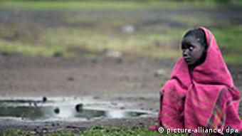 A young girl, wrapped in a blanket, sits in a field in Goma, DR Congo