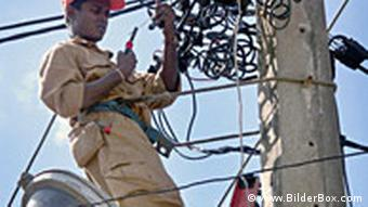 An electrician works on electric lines in Africa