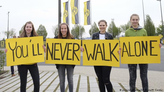 Vier weibliche BVB-Fans halten Plakate You'll never walk alone hoch (Foto: picture-alliance/AP Photo/M. Corder)